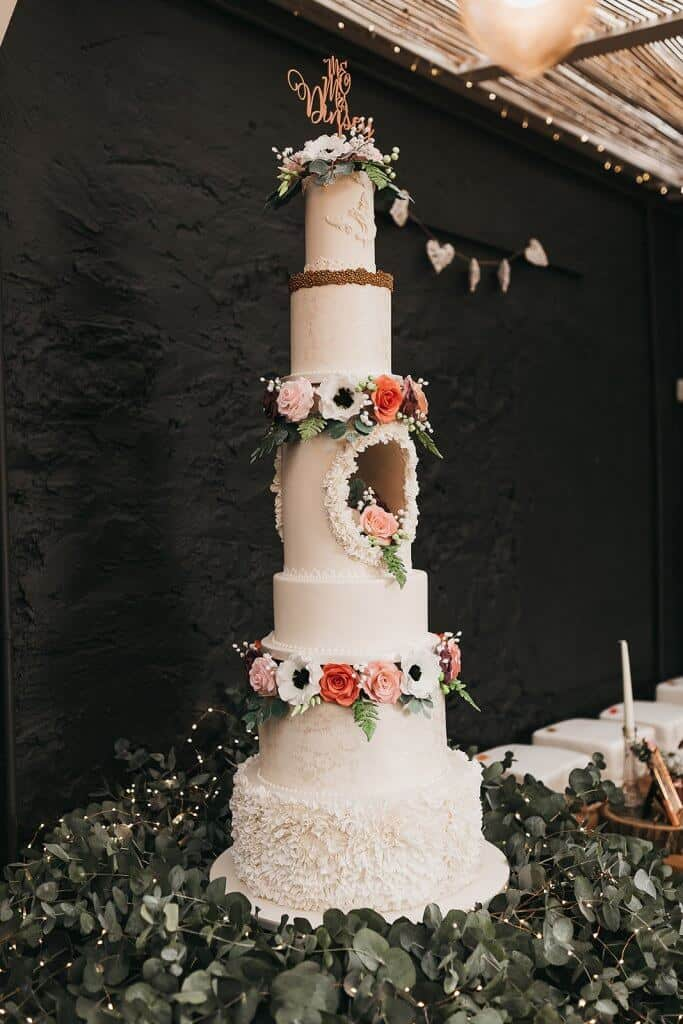 tall wedding cake with hole and flowers llys meddyg newport pembrokeshire